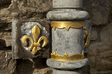 lis: A detail from an old lead drain pipe at Edinburgh Castle. The gold paint on the fleur de lis detail and pipe fittings provide a bit of brightness to the dull grey lead pipe.