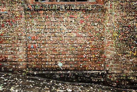 pike place: An old brick wall in Post Alley in the Pike Place Market in Seattle is covered with chewing gum deposited over a number of years. The gum is worked into names and other forms of graffiti.