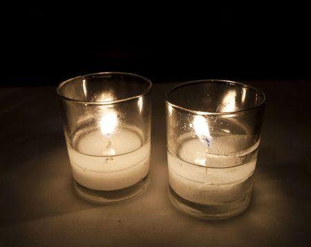 두 개의 불타는 촛불은 촛불 깜박임과 함께 저녁 식사를위한 낭만적 인 조명을 제공합니다. 스톡 콘텐츠