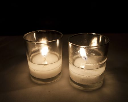 Two burning candles provide romantic illumination for a dinner with the flickering of candlelight. Stock Photo - 7462394