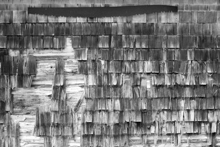Old wood shingles on a barn wall have weathered into a kind of mosaic patter. A rusty old saw is located at the top. (In black and white infrared.) Stock Photo - 7551152