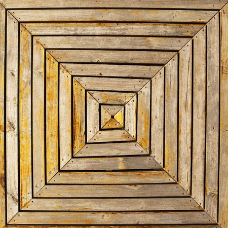 A cross, or X, pattern formed by wooden boards in an uneven square shape is the basis for a wooden deck near the harbor in Puerto Baquerizo Moreno in the Galapagos Islands of Ecuador.