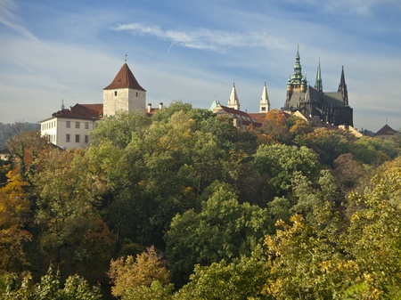 Prague Castle with the cathedral of St. Vitus and other spires from various palaces on a fall day where the leaves are just starting to turn color. photo