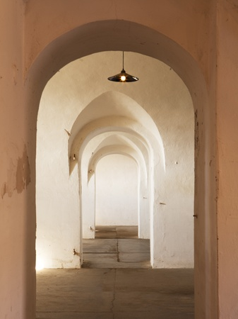 terezin: An interior hallway with repeating arches in one of the guards barracks of the World War II German prison camp at Terezin in Czechoslovakia. Now empty, the building is used for exhibits.