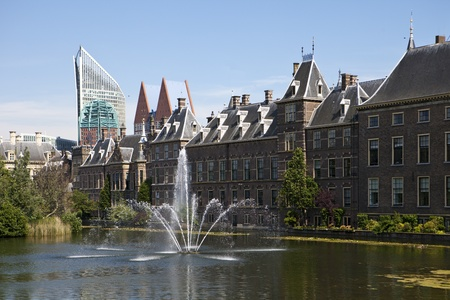 The exterior of the Binnenhof, or Netherlands Parliament building in The Hague, as viewed over the Hofvijver lake and fountain.
