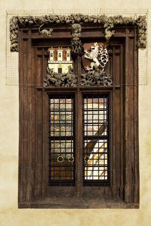 A window on the exterior of the City Hall building in Prague's Old Town main square. The castle and lion symbols represent Prague's history. The brighly painted interior is visible through the windowpanes. Stock Photo - 8698340