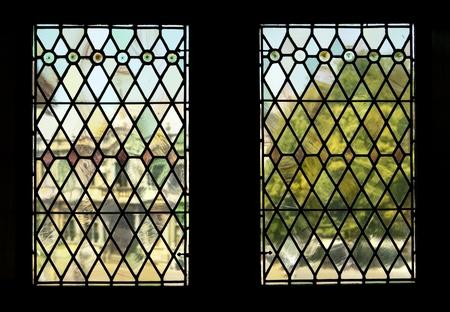 Het uitzicht door twee gebrandschilderde ramen in het landmark Brugge-stadhuis. De achtergrond van een gebouw en de boom in Burg Square wordt gerenderd in onduidelijk, bijna impressionistische tinten, door verstoringen van de oude deelvensters.