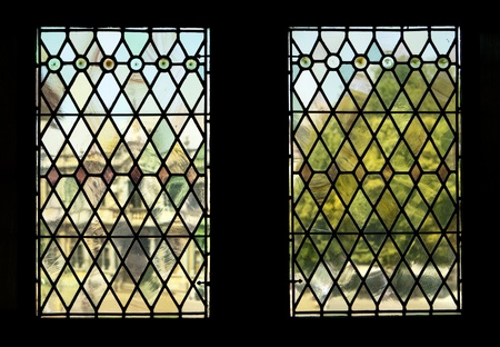panes: The view through two stained glass windows in the landmark Bruges Town Hall. The background of a building and tree in Burg Square is rendered in indistinct, almost impressionistic tones, through distortions from the old panes. Stock Photo