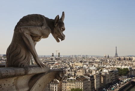 gargoyle: Stone gargoyle with horns peering over the city of Paris towards the Eiffel Tower while perched on a corner of the cathedral of Notre Dame.