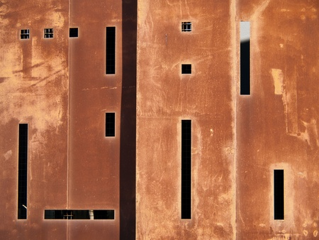 metal structure: The exterior of a building is a rusty, red color. The black shadows in the windows form an abstract pattern. Stock Photo