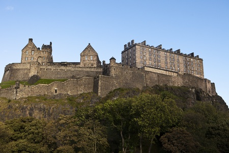 Edinburgh Castle rises above the city protected by natural cliffs and high rock walls. The guards stone barracks and other buildings are all part of the landmark structure. 免版税图像