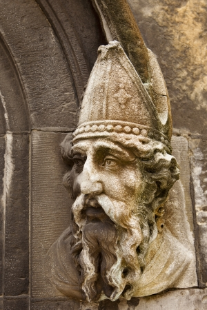 A stone carving of Saint Patrick on the lower door to the Chapel Royal of Dublin Castle in Dublin, Ireland. The stone is discolored with lichen and shows the effect of weather over the years.