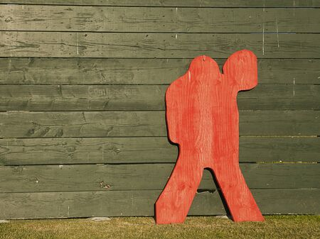 backstop: A red plywood shape in the form of a lacrosse goalie that is leaning up against a green backstop is used for target practice by the team. Stock Photo