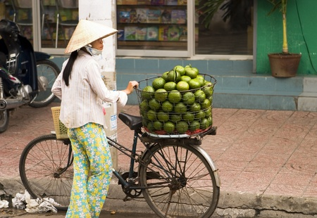 Ho Chi Minh City, Vietnam - September 27, 2006: A woman street vendor selling large green fruit on the streets of Ho Chi Minh City in Vietnam.