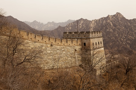 rugged terrain: A guardtower stands at the end of an extension of the Great Wall of China at Mutiany in the Beijing province. In the background, the steep mountains provide an indication of the rugged terrain. Stock Photo