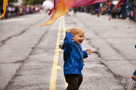 Seattle, Washington - June 18, 2011:  A small boy dancing under a banner on the parade route of the annual Fremont Solstice Day Parade. The parade celebrates the summer solstice.  Editorial