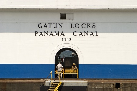 Gatun, Panama - April 11, 2007:  The central building at the Gatun Locks on the Panama Canal. The door provides a portal to view some of the equipment and the mountains in the background. Imagens - 10484627
