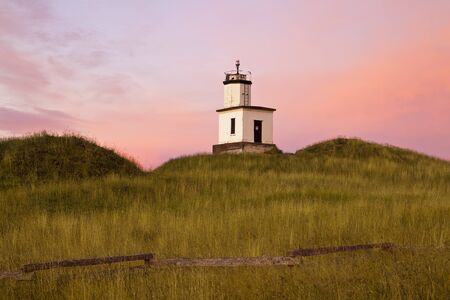 As the dawn sun comes up over the horizon, the lighthouse at Cattle Point on San Juan Island lights up as the sky behind glows with pink and magenta colors. photo