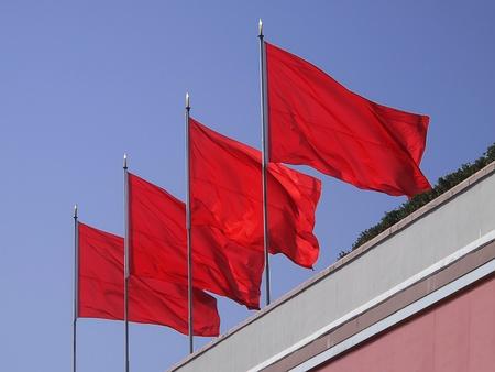 베이징 Tianment 광장에서 모택동 기념관의 상단에 오후 햇빛에 밝게 흔들며 네 개의 붉은 깃발.