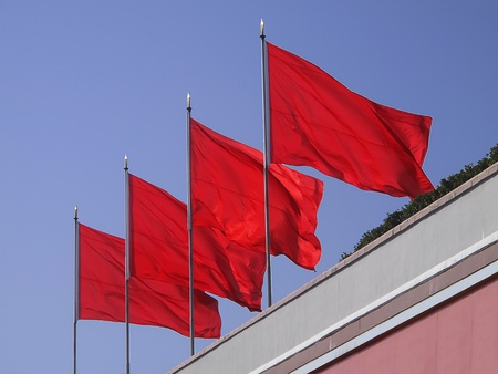 Four red flags waving brightly in the afternoon sun on the top of the memorial to Mao Tse Tung at Tianment Square in Beijing.