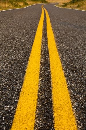 lineas rectas: Brillantes líneas amarillas, lo que indica una zona de no rebasar, desaparece en la distancia alrededor de una curva, mientras que separan los carriles en una carretera rural en San Juan Island.