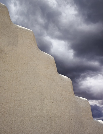 turmoil: Contrast between a white adobe wall and dark storm clouds in the background. Can be used as a symbol of calm and turmoil.