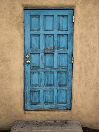 An old blue door in a adobe mud wall portrays an element of decay with layers and layers of peeling paint and cracks.