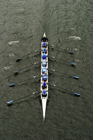 An eight person shell with a coxswain rowing in races on Lake Washington. As they row in unison, the boat cuts through the water. photo