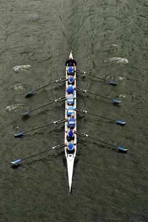 Un obus de huit personnes avec un aviron barreur dans les courses sur le lac Washington. Comme ils ramer à l'unisson, les coupes en bateau à travers l'eau.