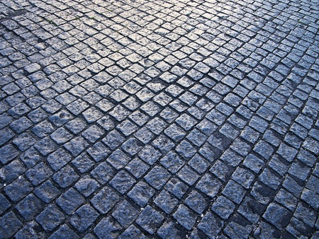 Square cobblestones, slightly polished from traffic, show a reflection from the sun at dusk on a street in the Alfama district of Lisbon. photo