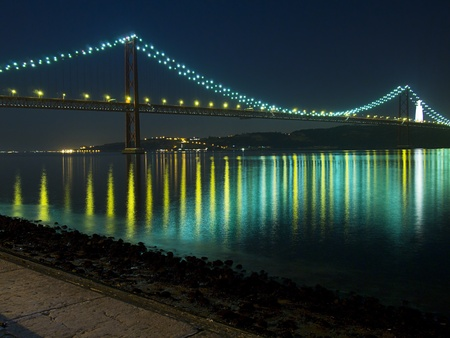 Night view of the April 25 (25 de Abril) Bridge in Lisbon, Portugal as seen from the Belem district. Completed in 1966 , this suspension bridge across the Tagus River is the longest central span in Europe. Originally named after dictator Salazar, the name photo