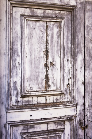 A detail view of an old, weather-beaten wood door with layers of peeling gray paint results in a distressed, weathered texture. photo