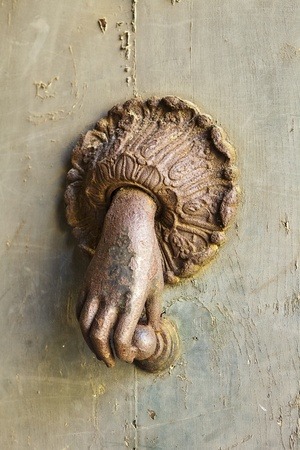 A mysterious hand comes out of the door to hold a knocker. This rusty ornamental fixture was seen on a door in Orvieto, Italy. Stock Photo - 12048318