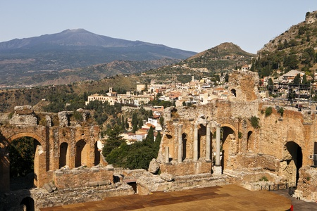 taormina: A view from high up in the cheap seats in the ancient Roman theatre or Teatro Antico of Taormino in Sicily shows the city and then the cone of the Mt. Etna volcano in the distance.