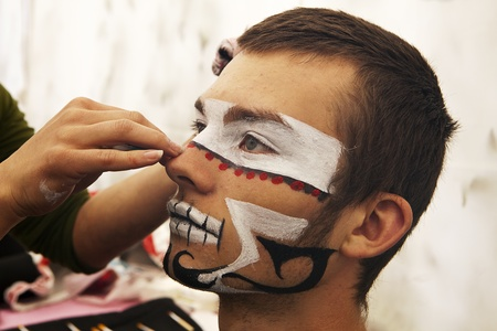 SEATTLE, WASHINGTON - JUNE 18, 2011: A unidentified young man sits and is made up in costume prior to performing with the Ice Queens of Ukon Julha ensemble in the 2011 Fremont Solstice Day Parade in Seattle on June 18, 2011. The parade marks the start of