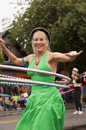 solstice: SEATTLE, WASHINGTON - JUNE 18, 2011: An unidentified young woman in the All City Hoopers ensemble dances with a hula hoop in a performance in the Annual Fremont Summer Solstice Day Parade on June 18, 2011.  The parade marks the start of summer in Seattle.