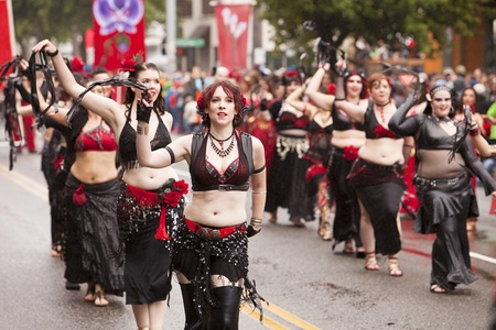 solstice: SEATTLE, WASHINGTON - JUNE 18, 2011: The Visionary Belly Dancers march in black leather and red lingerie on June 18, 2011 in the Annual Fremont Summer Solstice Day Parade. The parade marks the start of summer in Seattle. Editorial