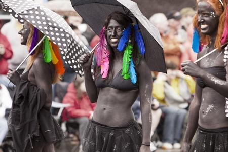 body paint: SEATTLE, WASHINGTON - 18 de junio de 2011: Tres mujeres no identificadas marchan en el desfile anual de Fremont día del solsticio de verano el 18 de junio de 2011, como llevan a cabo en la pintura del cuerpo negro, bikinis y plumas de colores. El desfile marca el inicio del verano en Seattle. Editorial