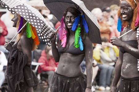 SEATTLE, WASHINGTON - JUNE 18, 2011: Three unidentified women march in the Annual Fremont Summer Solstice Day Parade on June 18, 2011 as they perform in black body paint, bikinis and colorful feathers. The parade marks the start of summer in Seattle. Stock Photo - 12059956