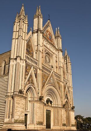 orvieto: The front facade of the Orvieto Cathedral is ornate and detailed with colorful mosaics, intricate carvings, bronze statues, bell towers and more. It is a magnificent example of 14th century Italian architecture that evolved from Romanesque to Gothic. Editorial