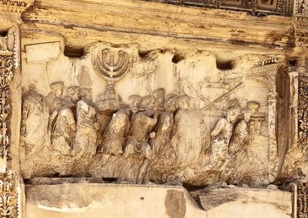 Das Wandrelief an der Titusbogen zeigt römische Soldaten, die Beute aus der Zerstörung des Tempels von Jerusalem im Jahre 70 n. Chr. einschließlich des Golden Temple Menorah, die Tabelle der Schaubrote und die silbernen Trompeten, die Juden nach dem festiva genannt Editorial