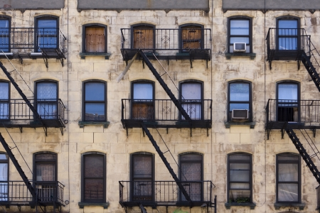 old building facade: Three floors of windows with fire escapes on the facade of a New York apartment building that is in desperate need of paint and repairs.