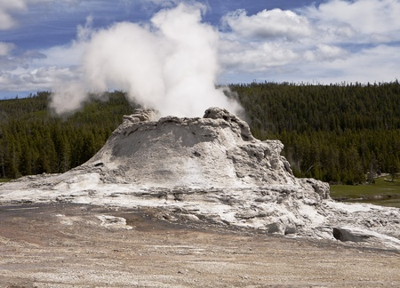 erupt: Castle Geyser is one of the larger volcanic geysers in Yellowstone National Park. With a large cone formed after years of eruptions, this viewpoint shows steam rising from the top vent. Stock Photo