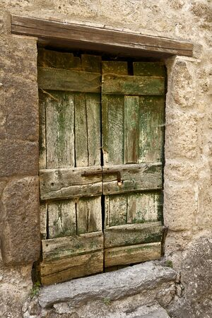 A rough-hewn and weathered cellar door in the hill town of Civita in Umbria, Italy. The green paint on the wooden door is peeling and faded. Stock Photo - 12387820