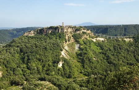 The medieval Italian hill town of Civita has been near isolated through earthquakes. The pedestrian bridge, as viewed from the town of Lubriano across the valley, is the only link from the clifftop village to the nearest town. Stock Photo