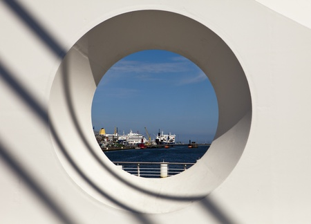 An architectural abstract view through a structural detail on the Samuel Beckett bridge in Dublin. Dublin harbor and ships are visible through the porthole-like circle with shadows arcing across the white background.