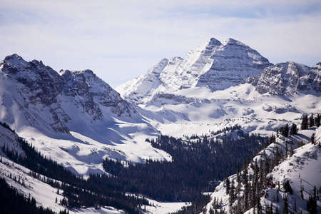 A winter view of the Maroon Bells mountain peaks in Colorado from a nearby mountain