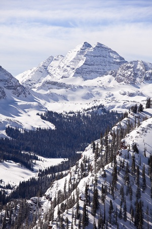A winter landscape view, in vertical format, of the two peaks in the Maroon Bells massif in Colorado