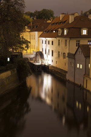 nighttime: A night view of one of the canals in Prague as seen from the Charles Bridge  At the end, an old water wheel is slowly turning, creating a blur in the evening light