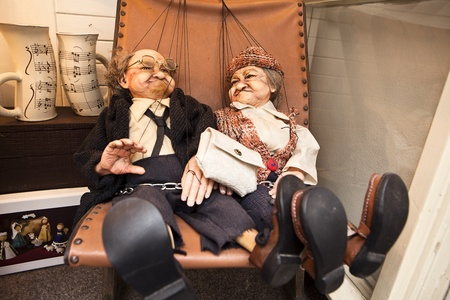 puppet woman: Two ornamental puppets or marionettes sit together and recline in a storefront window